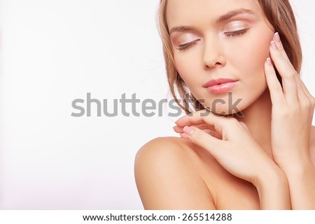 Young pleased woman with natural makeup touching her face #265514288