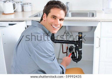 Young plumber fixing a sink