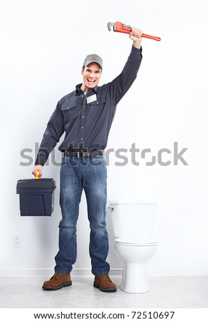 Young plumber near a flush toilet