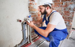 Young plumber, wearing blue uniform and white helmet working with sealant fix of sewer pipe in kitchen or in bathroom in unfinished apartment. Concept of plumbing works and home renovation