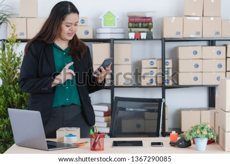 Young, plump, beautiful, long black hair, Asian business lady, in smart casual, standing behind of her work station, browsing smartphone, at startup home office, with notebook and office background