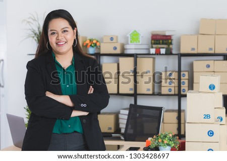 Young, plump, beautiful, long black hair, Asian business lady, in smart casual, standing in front of her work station, arms crossed, at startup home office, with notebook and office background