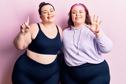 Young plus size twins wearing sportswear showing and pointing up with fingers number six while smiling confident and happy.