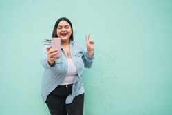 Young plus size woman taking selfies with phone.