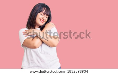 Young plus size woman wearing casual clothes hugging oneself happy and positive, smiling confident. self love and self care  Foto stock ©