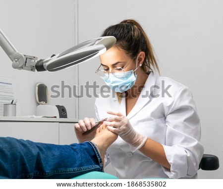 Young podiatrist doing chiropody in her podiatry clinic. The chiropodist is cutting the patient's nails with specialized scissors Stockfoto ©