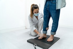 Young podiatrist in her clinic examining a patient's feet on a pressure platform. The podiatrist is bent over and placing the patient's foot in the mold.