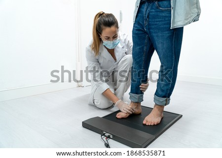 Young podiatrist in her clinic examining a patient's feet on a pressure platform. The podiatrist is bent over and placing the patient's foot in the mold. Stockfoto ©
