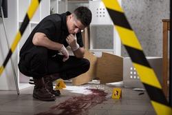 Young policeman collecting evidence standing behhind yellow crime scene tape