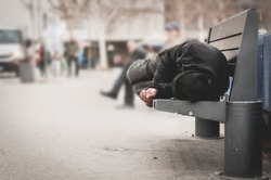 Young poor dirty homeless man or refugee sleeping on the wooden bench on the urban street in the city, social documentary concept