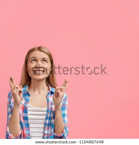 Young positive European female with broad warm smile, crosses fingers while makes wish, hopes dreams come true, wears casual checkered shirt, isolated over pink background with copy space aside