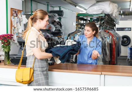 Young positive female worker of dry cleaner checking clothes of customer on reception