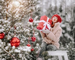 Young positive pretty woman in stylish warm clothing sitting with holiday gift near decorated Christmas tree. Outdoors sending air kiss in winter snowy forest and beautiful nature at background
