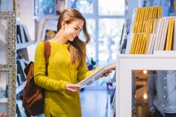 Young positive student american woman in yellow sweater buying souvenirs in gift shop.