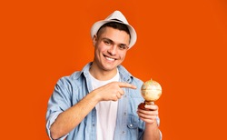 Young positive tourist holding globe, pointing to desirable destination of his trip, orange background. Travel concept.