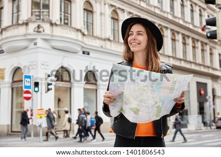Young positive tourist holds travel paper map, reads route of trip, goes sightseeing, searches destination, gets to right place wears black headgear and leather jacket focused away with pleasant smile