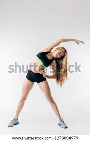 Young positive woman doing side bend with arms. hobby, lifestyle, spare time, free time