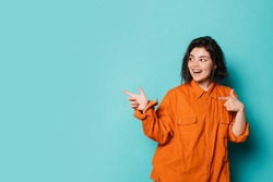 Young positive woman stand on left side and point to right with index fingers. Isolated over blue background. Cheerful happy teenager girl in orange shirt posing on camera