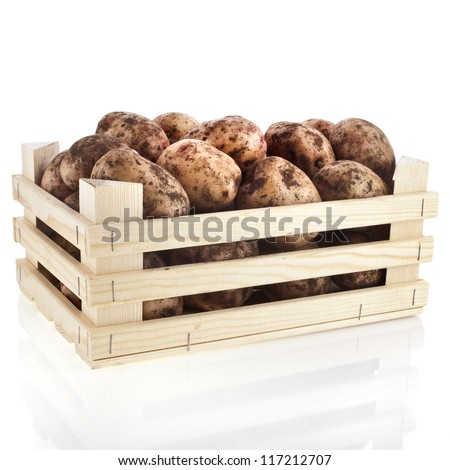 young potatoes in a wooden box crate isolated on white