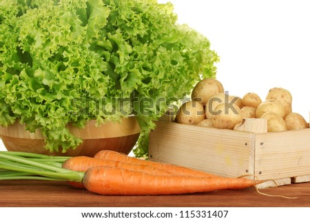 young potatoes in a wooden box with lettuce and carrots on a table on white background close-up