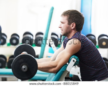 Young powerful muscular bodybuilder training with weight at sporting gym