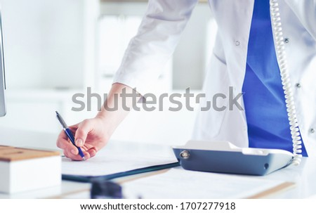 Young practitioner doctor working at the clinic reception desk, she is answering phone calls and scheduling appointments Photo stock ©