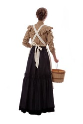 Young prairie woman holding a basket walking away isolated on white