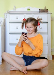 Young pre-teen girl in the bright orange  jacket with funny pigtails plaing with a mobile phone and making self-portrait and snapchat, sitting on the floor at the home