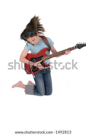 Young pre teen girl jumping up and playing a red electric guitar.