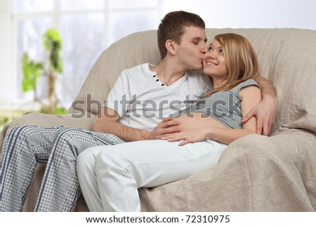 Young pregnant couple sitting on a sofa in a room - stock photo