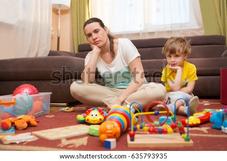 Young pregnant mother and her little son, at home. Mother and little son  sit on a floor. Mom tired to tidy up the house. Child scattered toys. Mess in the house. Mother has quarreled with the son. #635793935