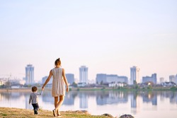 Young pregnant mother walking with her little son in summer near the lake. City. Sunset. Mother holding baby 's hand