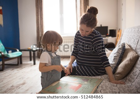 young pregnant mother with dreadlocks, and her son play and reading a book, lifestyle, real interior toning