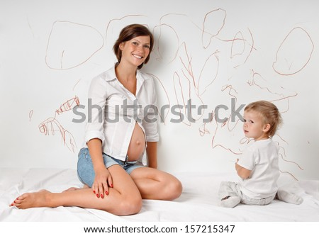 young pregnant mother with her son on white bed about the wall