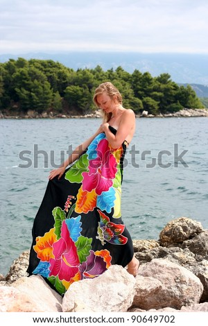 Young pregnant smiling woman dressed in colored pareo looks down