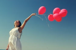 Young pregnant woman holding red balloons. Photo in old color image style.
