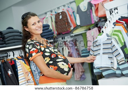 Young pregnant woman in colorful shirt choosing clothes at shopping store