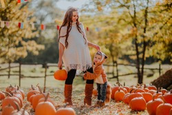 Young pregnant woman in white autumn cardigan and red boots posing with a little son in fox coat at the pumpkin's field. Fall background.