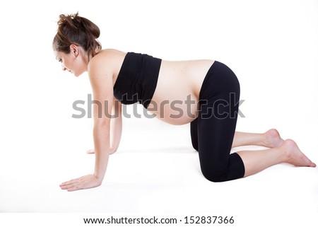 Young pregnant woman practises yoga asana