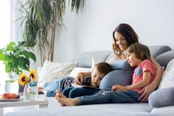 Young pregnant woman, reading a book at home to her two boys, eating fruits, hugging and laughing