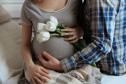 Young pregnant woman sitting with husband and holding flowers in room