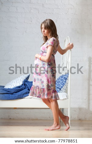 Young pregnant woman standing near the bed