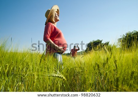 Young pregnant woman waiting her man in the wheat field.