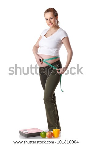 Young  pregnant woman with scales and fruit on a white background.  Concept of healthy lifestyle.