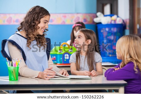 Young preschool teacher teaching little girls in classroom
