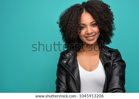 Young pretty African American millennial woman with natural curly hair wearing fashionable white tank top and black leather jacket smiling. Blue  Background.  #1045913206