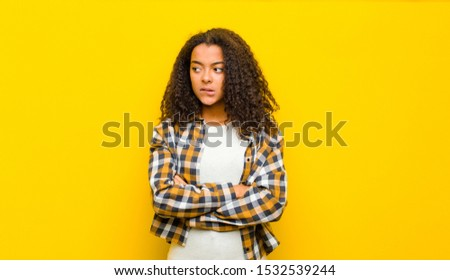young pretty african american woman doubting or thinking, biting lip and feeling insecure and nervous, looking to copy space on the side against yellow wall