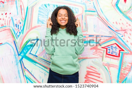 young pretty african american woman feeling nervous and hopeful, crossing fingers, praying and hoping for good luck against graffiti wall #1523740904