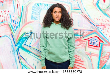 young pretty african american woman looking puzzled and confused, biting lip with a nervous gesture, not knowing the answer to the problem against graffiti wall