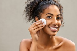 Young pretty african american woman taking off makeup with cotton wipe sponge. Smiling girl cleaning face isolated over background. Black young woman cleansing face, daily healthy beauty routine.